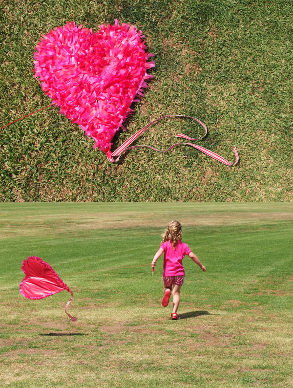 girl in pink running with heart kite on grass