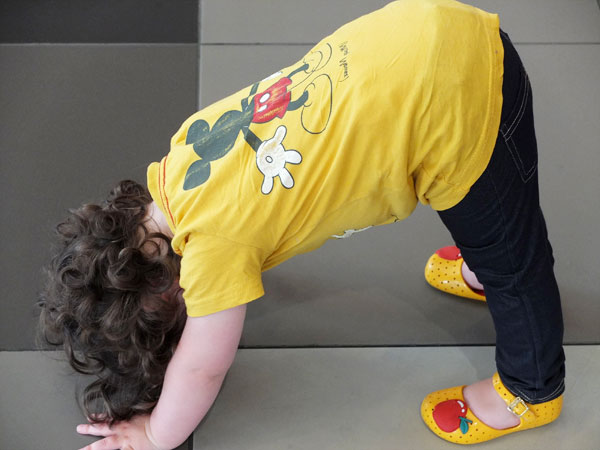 Child attemting a handstand wearing a yellow mickey mouse t-shirt