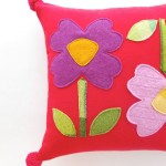 Giant flower applique cushion finished with pom pom